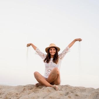 모래에 앉아 전체 샷된 웃는 여자