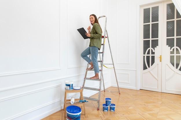 はしごの上に立っているフルショットの笑顔の女性