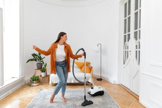 カーペットを掃除機で掃除するフルショットのスマイリー女性