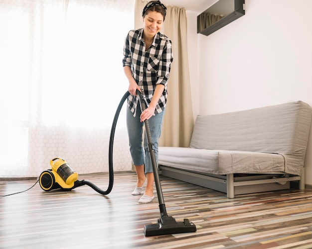 Full shot smiley woman vacuuming