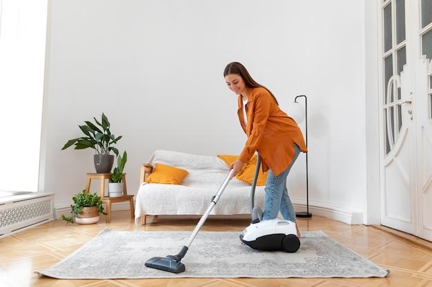 Full shot smiley woman vacuuming