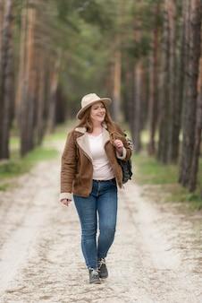 자연 속에서 걷는 전체 샷 웃는 여자