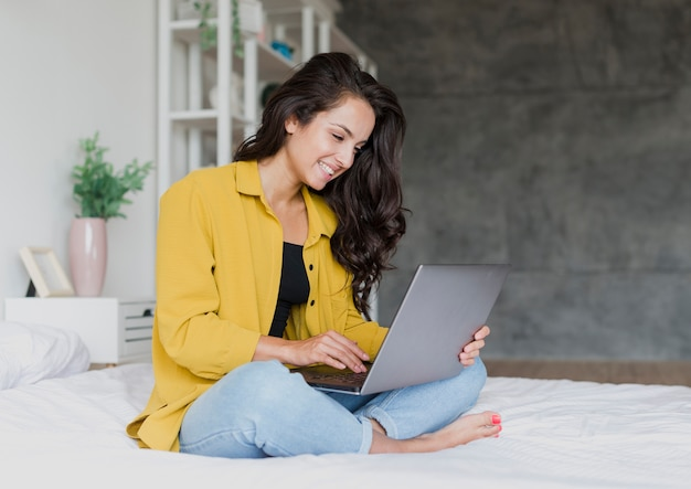 Full shot smiley woman with laptop