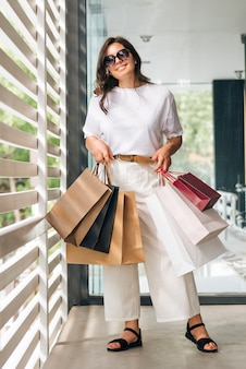 Full shot smiley woman with shopping bags
