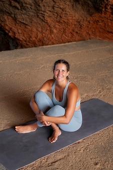 Donna sorridente a tutto campo sul tappetino da yoga