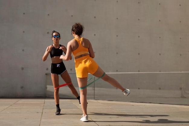 屋外でトレーニングするフルショットのスマイリー女性