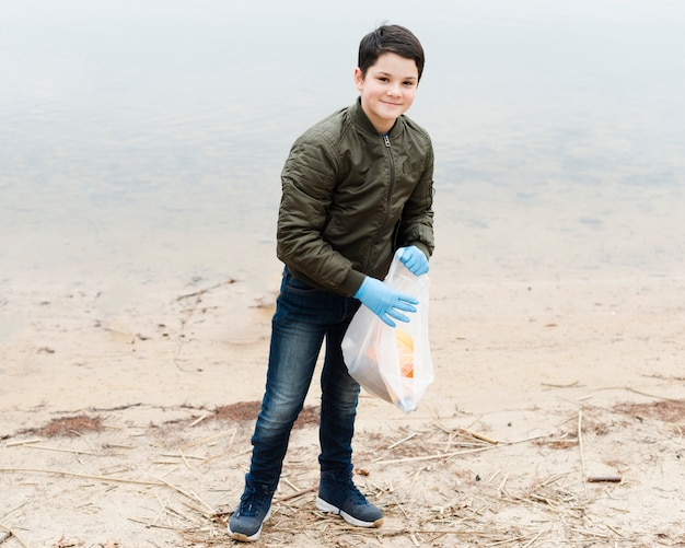 Full shot of smiling boy with plastic bag
