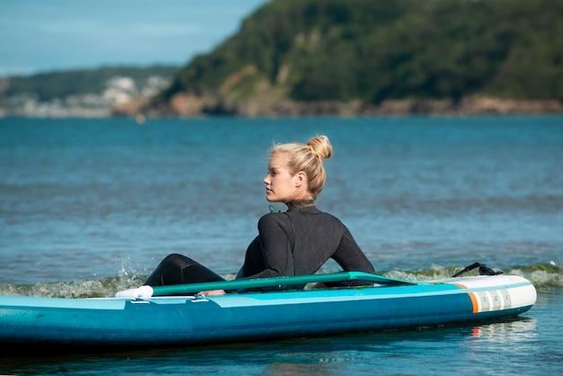 Full shot sportswoman paddleboarding