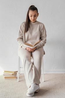 Полный кадр студент, читающий на стуле