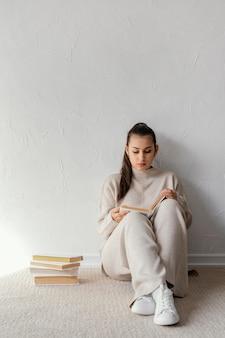 Полный кадр студент, читающий на полу