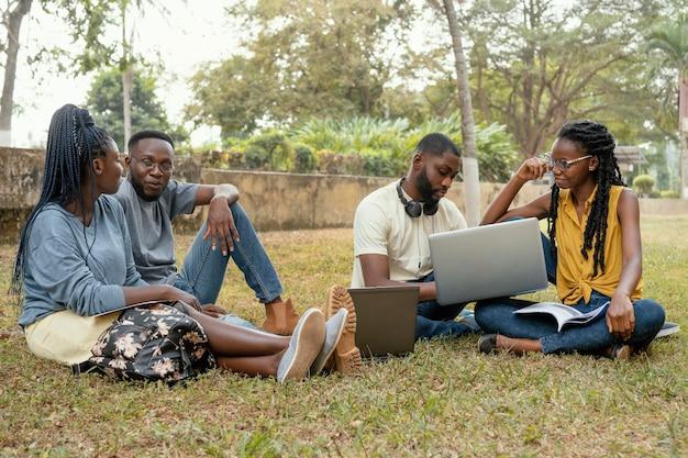 Studenti del colpo pieno che si siedono sull'erba