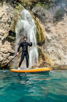 Full shot surfer holding paddle
