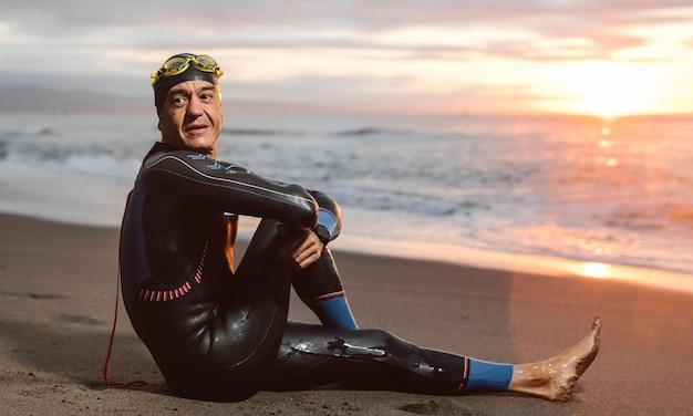 Full shot swimmer sitting on beach