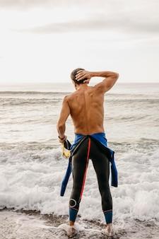 Nuotatore pieno del colpo che sta in acqua