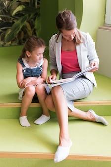 フルショットの先生と本を持つ少女