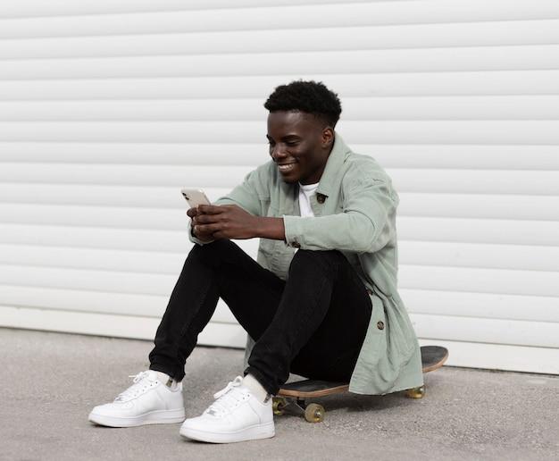 Teenager pieno del colpo che si siede sullo skateboard all'esterno