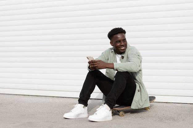 Teenager pieno del colpo che si siede sullo skateboard con il telefono