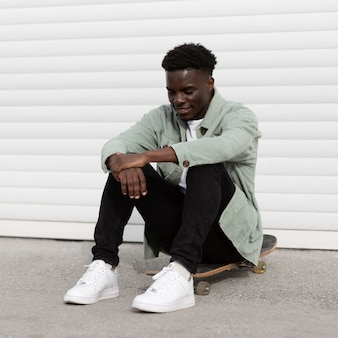 Teenager pieno del colpo che si siede sullo skateboard