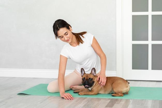 Подросток и собака в полный рост на коврике для йоги
