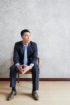 Full shot of thoughtful adult businessman sitting on chair