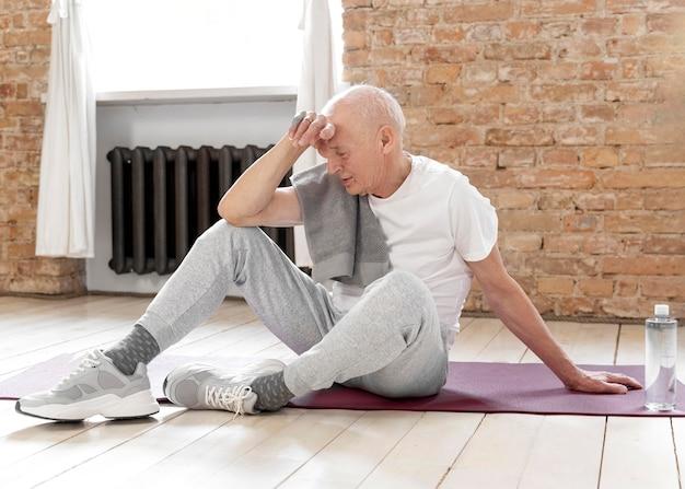 Uomo anziano stanco del colpo pieno sulla stuoia