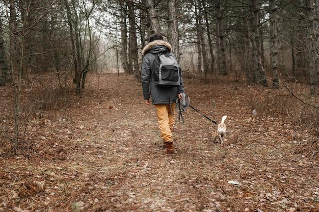 Путешественник в полный рост в лесу с милой собакой