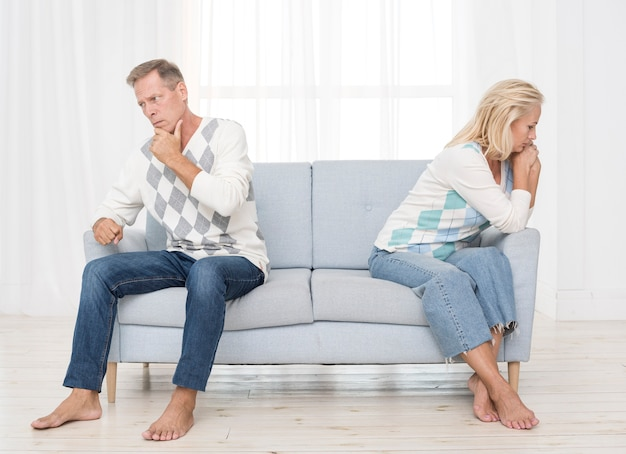 Full shot upset couple sitting on the couch