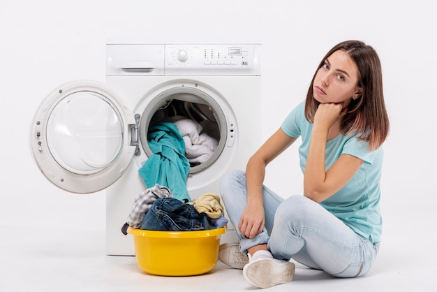 Full shot upset woman sitting near washing machine