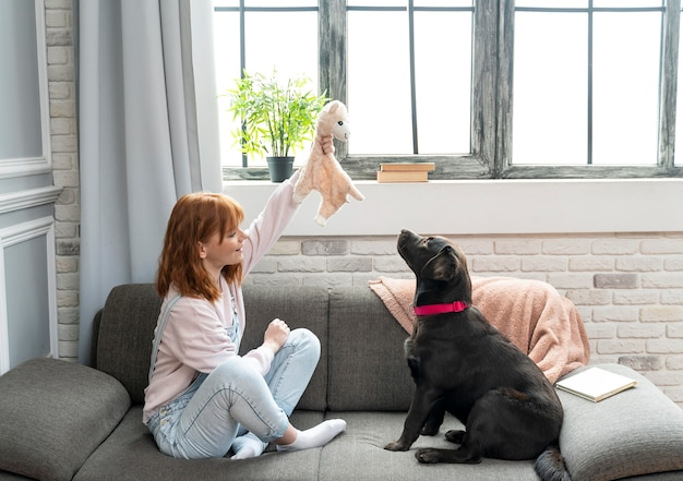 Full shot woman and adorable dog on couch