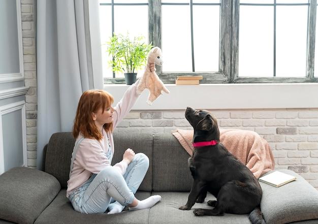 フルショットの女性とソファの上の愛らしい犬