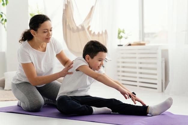 Женщина и мальчик в полный рост на коврике для йоги