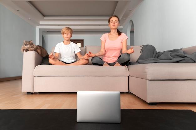 Полный выстрел женщина и ребенок медитируют