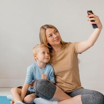 Полный снимок женщины и ребенка, делающего селфи