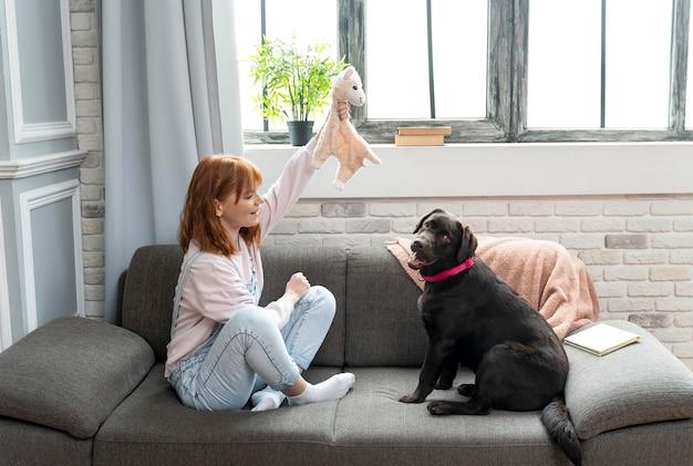 フルショットの女性とソファの上のかわいい犬