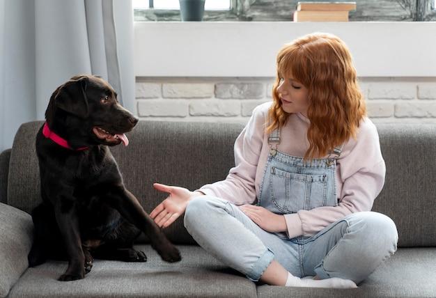 フルショットの女性とソファの上の犬