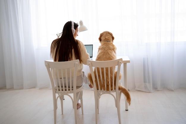 椅子に座っているフルショットの女性と犬