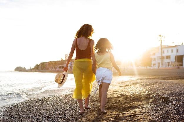 ビーチでフルショットの女性と女の子