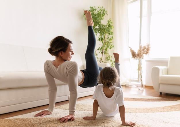 Полный снимок женщина и девушка, тренирующаяся в помещении