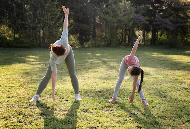 Полный снимок женщина и ребенок упражнения на открытом воздухе