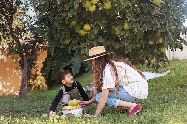 フルショットの女性と芝生の上の子供