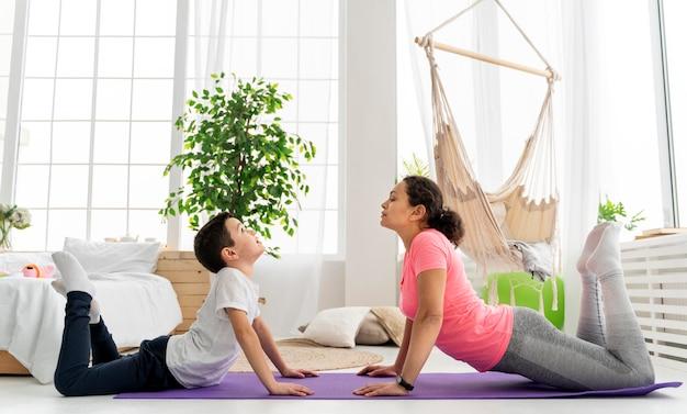 Женщина и ребенок в полный рост на коврике для йоги
