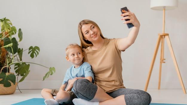 Полный снимок женщина и ребенок, делающий селфи
