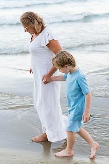フルショットの女性とビーチで歩く子供