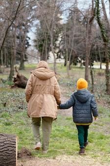 전체 샷 여자와 아이가 함께 걷는