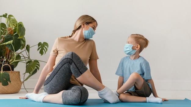 フルショットの女性とフェイスマスクを身に着けている子供