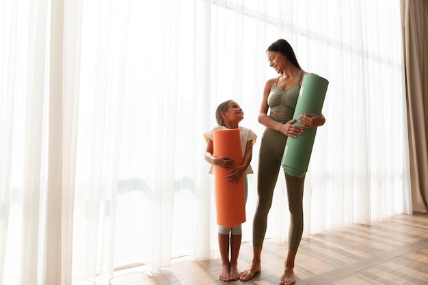 Женщина и ребенок в полный рост с ковриком для йоги