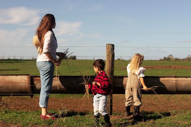 自然の中でのフルショットの女性と子供たち
