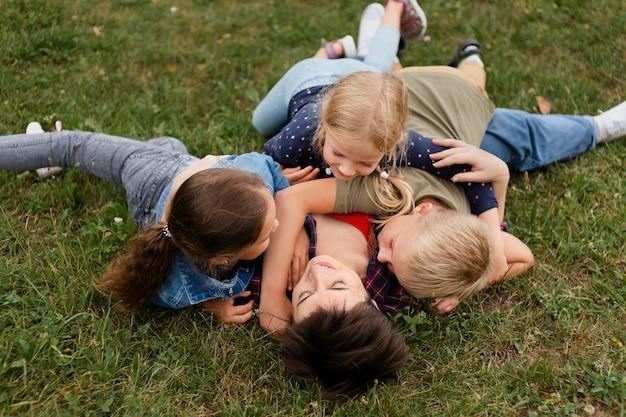 フルショットの女性と草の上に横たわる子供たち