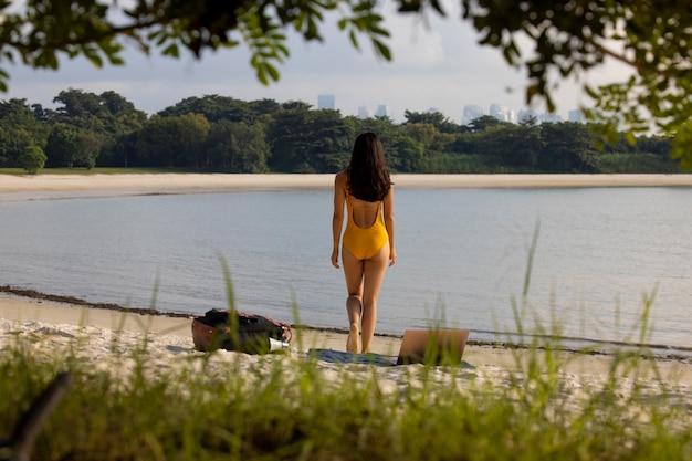 노트북으로 해변에서 전체 샷 여자