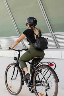 Donna del colpo pieno sulla bici che indossa il casco